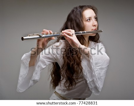 girl plays the flute on a grey background - stock photo