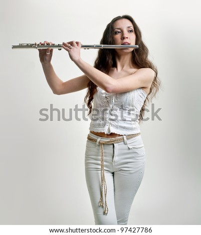 girl plays the flute on a white background