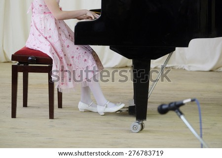 girl plays the piano during a concert - stock photo