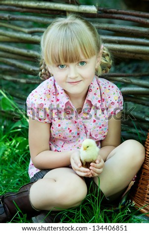 Girl plays with chicken - stock photo