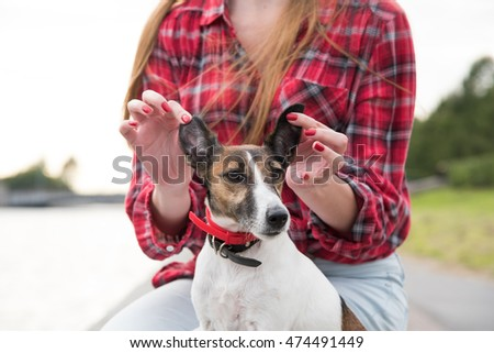 girl plays with her dog outdoor, funny posing.