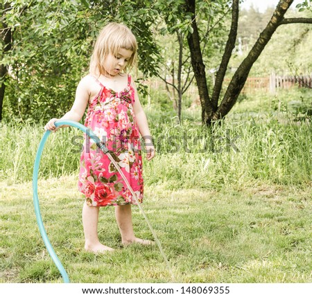 Girl plays with water hose - stock photo