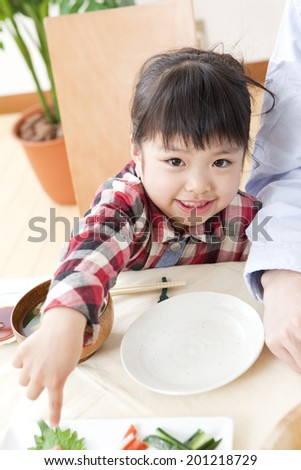 Girl pointing at sushi - stock photo