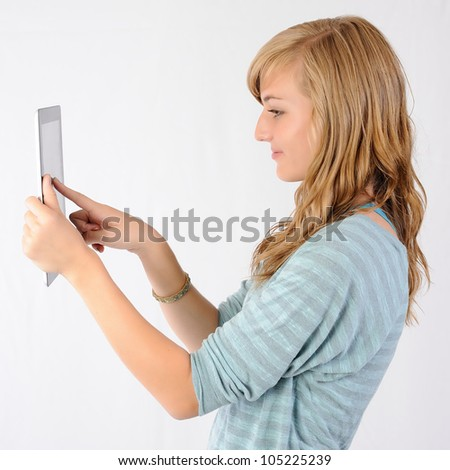 Girl Pointing at Tablet Computer. Thirteen year old girl touching the screen of a tablet computer. Note: Not Isolated. - stock photo