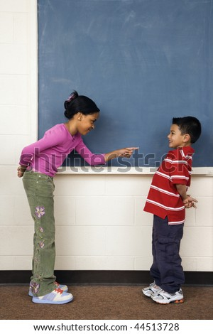 Girl pointing finger at boy in school classroom. Vertically framed shot. - stock photo