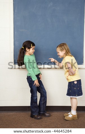 Girl pointing finger at other girl in school classroom. Vertically framed shot. - stock photo