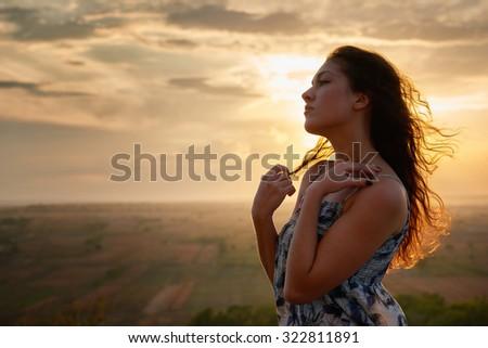 girl portrait at sunset on plain background - stock photo