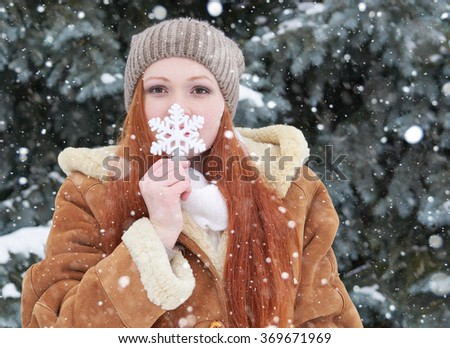 Girl portrait at winter outdoor, snowy weather, showing big snowflake toy. - stock photo