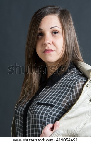 Girl portrait in cotton jacket. Young beautiful woman on wall background. Fashion female portrait. On a gray background - stock photo