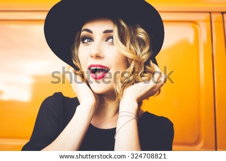 girl portrait of a beautiful young blonde in a black hat with red lips, bright makeup on orange background car smiling and posing lifestyle - stock photo