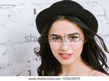 Girl portrait of a beautiful young brunette in a black hat - stock photo