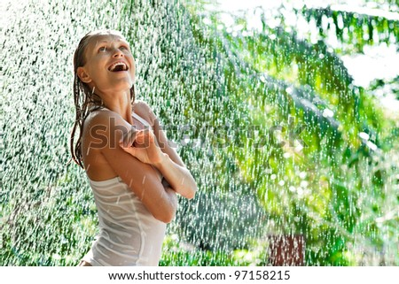 Girl portrait stay outside under in rain drops in tropical forest