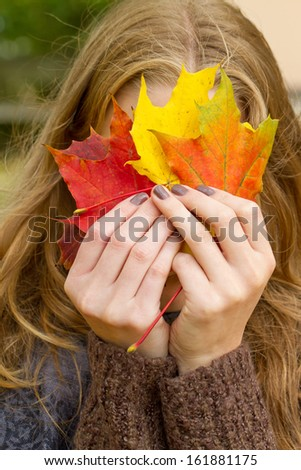 Girl portrait with full face covered by a autumn leaves - stock photo