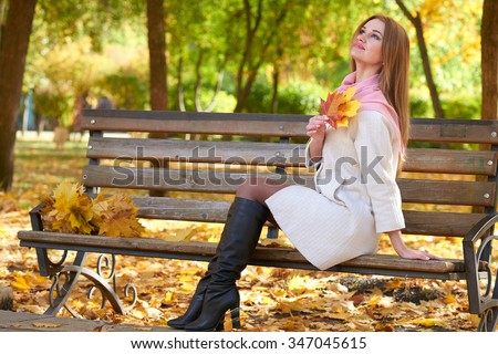 girl portrait with leaves in autumn city park
