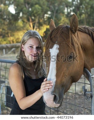 Girl poses with horse during sunset - stock photo