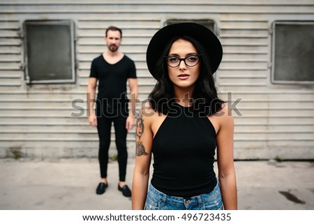 girl posing against a background of a Man and wall