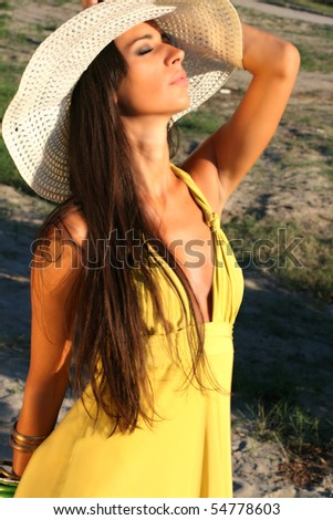 Girl posing in the sun with beautiful hat - stock photo