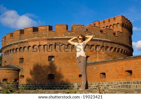 Girl posing near ancient fort - stock photo