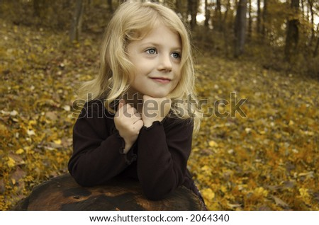Girl posing on a tree stump - stock photo