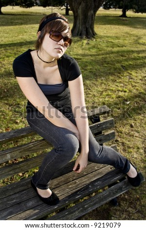 Girl posing on bench in park - stock photo