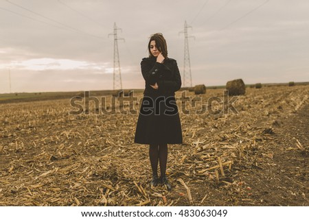 Girl posing on field. Dark. Hipster. Gothic.