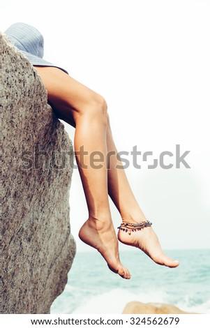 Girl posing on the rocks alone on the ocean seashore. Outdoors lifestyle portrait - stock photo