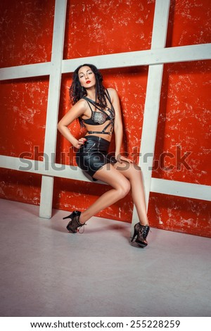 Girl posing sitting on a red background, it is in leather skirt and sword belt straps on the chest. - stock photo