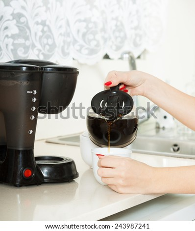 girl pouring strong coffee in the kitchen - stock photo