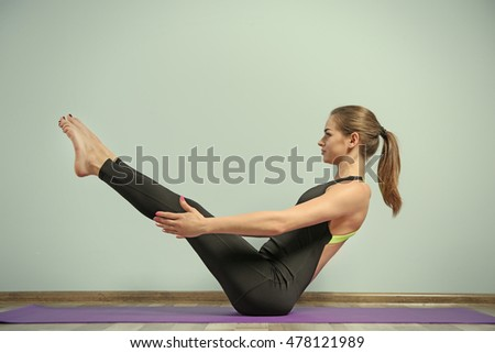 Girl practicing advanced yoga on blue wall background