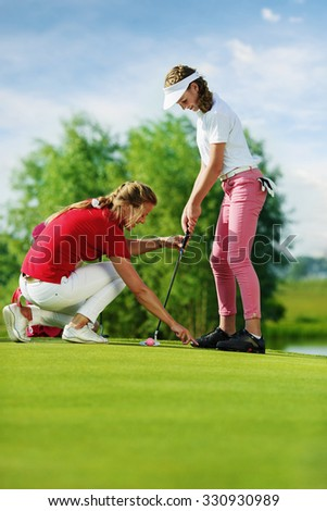 Girl practicing with trainer at golf school at summer day - stock photo