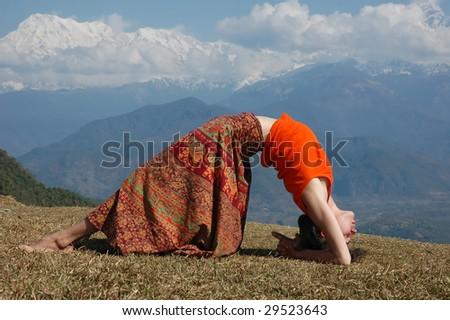 Girl practicing yoga in mountains. Bridge. - stock photo