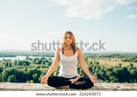 girl practicing yoga on roof. Yoga in the park