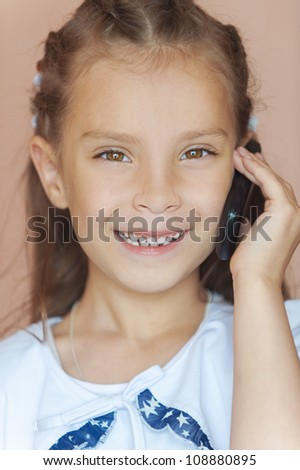 Girl-preschooler talking on cell phone, on pink background. - stock photo