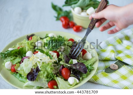 girl prick cherry tomato salad on a fork - stock photo