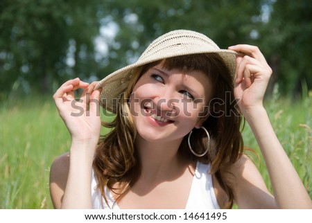 girl protects her hair from the sun with a hat