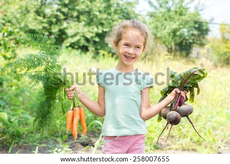 Girl pulled out a carrot from the garden - stock photo