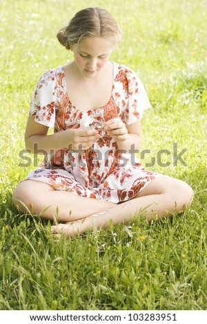 Girl pulling petals off a daisy flower while sitting on a green field, playing love me, love me not. - stock photo