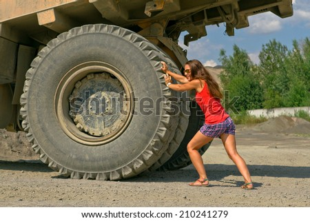 girl pushes BelAZ - stock photo