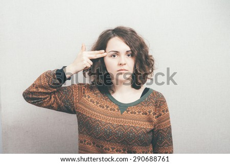 girl put her finger to her head - stock photo