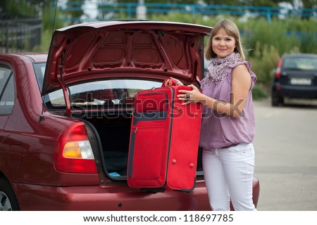 Girl puts the suitcase in the trunk of car - stock photo