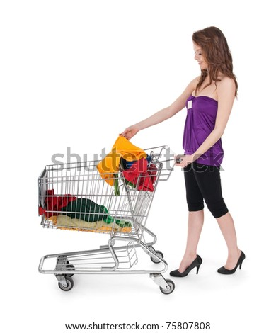 Girl putting colorful clothes in a shopping cart, isolated on white.