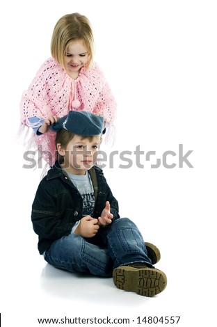 Girl putting hat on boy