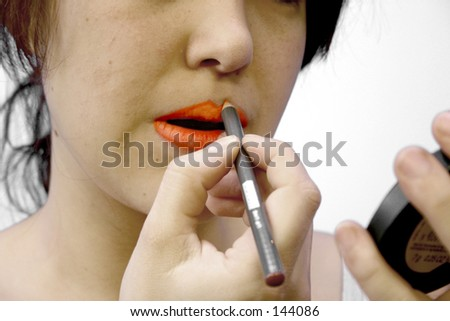 Girl putting make up in front of a mirror