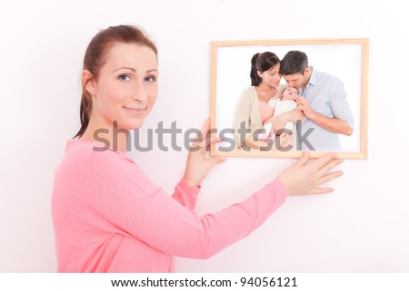 girl putting photo frame on wall - stock photo