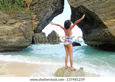 Girl raising her hands and enjoying nature by the sea. - stock photo