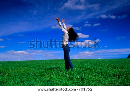 Girl reaches out to the sky on a grass field. - stock photo