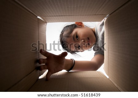 girl reaching for something inside the box - stock photo