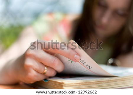 Girl read book in garden - stock photo