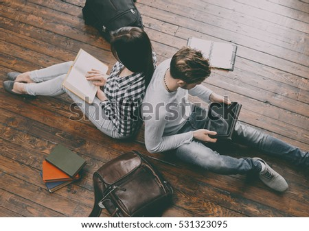 Girl reading a book and boy with a tablet sitting and studying on a floor. Vintage filter.