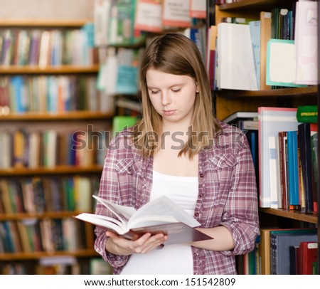 girl reading a book at the library